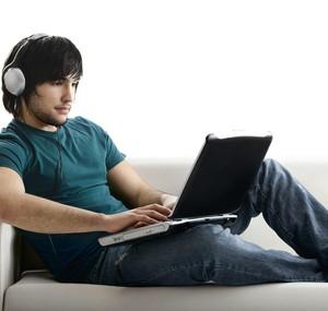Ein junger Mann sitzt auf einem Sofa und schaut sich Videos auf YouTube an