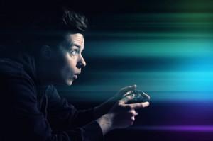 Ein junger Mann beim Spielen an einer Konsole bestrahlt vom bunten Licht