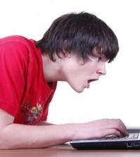 Ein Junge guckt entsetzt auf seinen Laptop