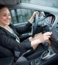 Frau schaltet im Auto die Musik an