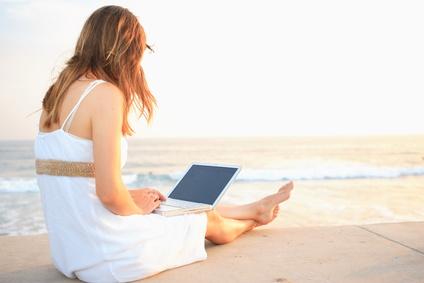 Frau am Strand mit einem Ultrabook