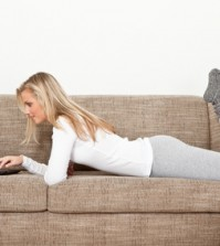 jung frau mit laptop auf dem sofa
